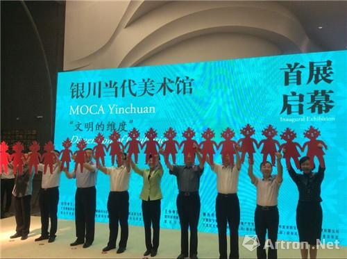 开幕典礼结束,嘉宾举起手拉手的当地著名的小红人剪纸
